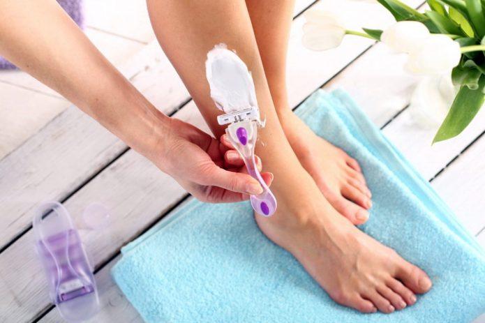 Женщина бреет ногу станком