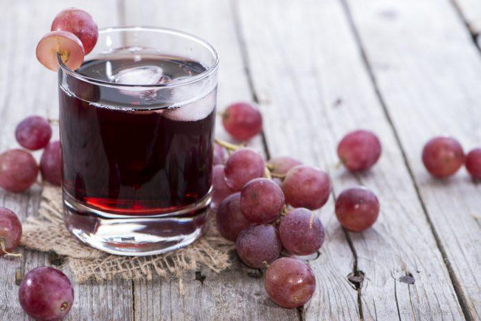Ягоды винограда и сок в стакане