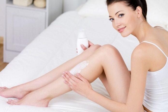 Девушка наносит крем на ногу