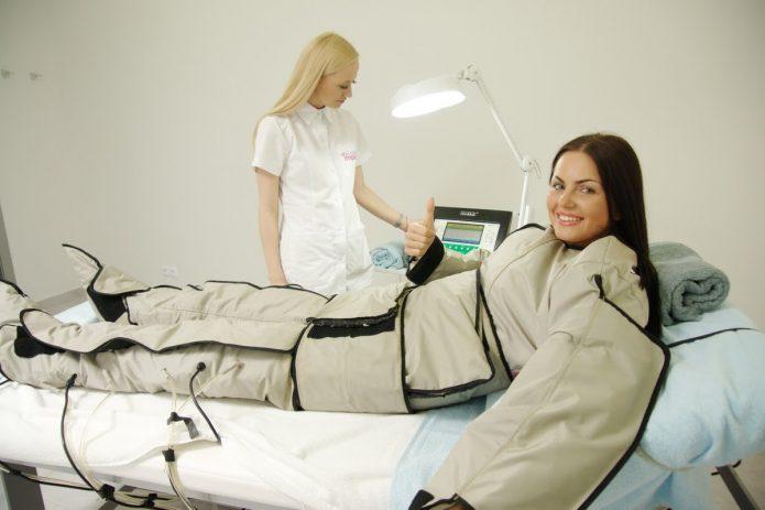 пациентка в лимфодренажном костюме лежит на кушетке для массажа