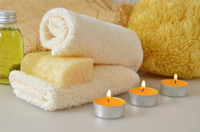 Масло, полотенце и свечи на столе
