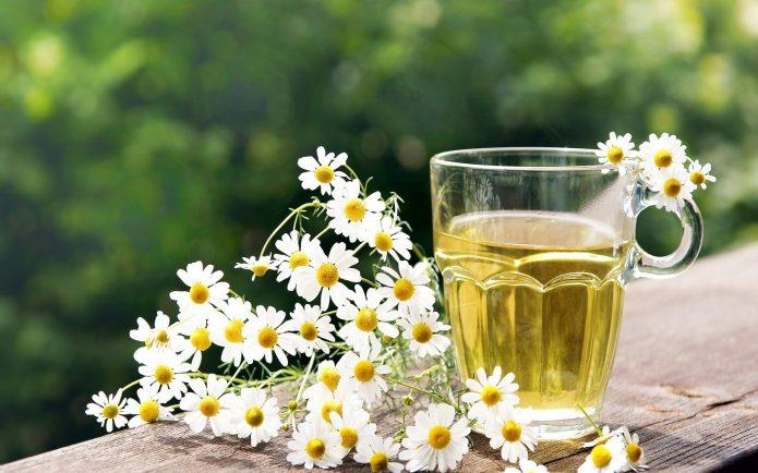 Отвар ромашки в стакане и цветы