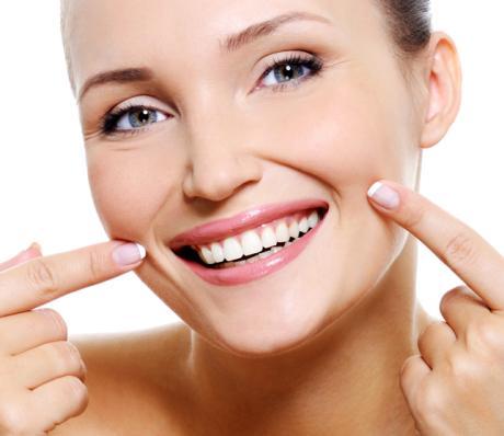 Женщина широко улыбается и держит указательные пальцы на щеках