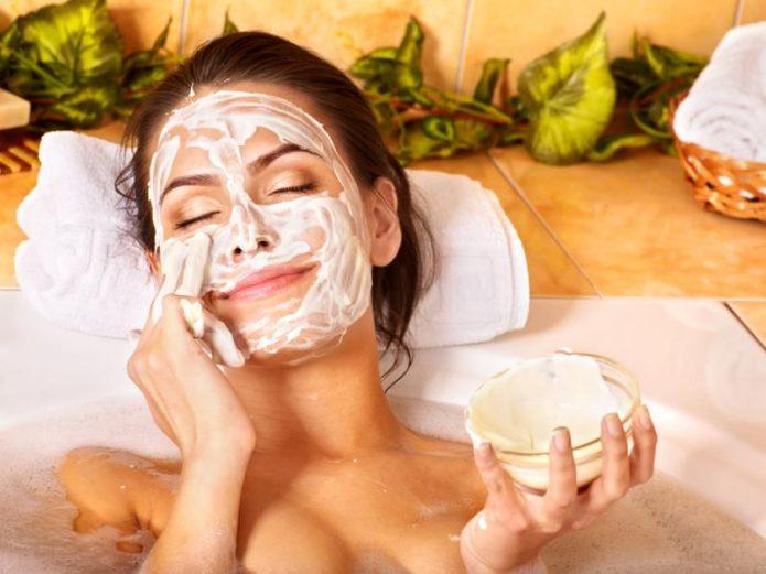 Лёжа в ванной, женщина наносит маску на лицо