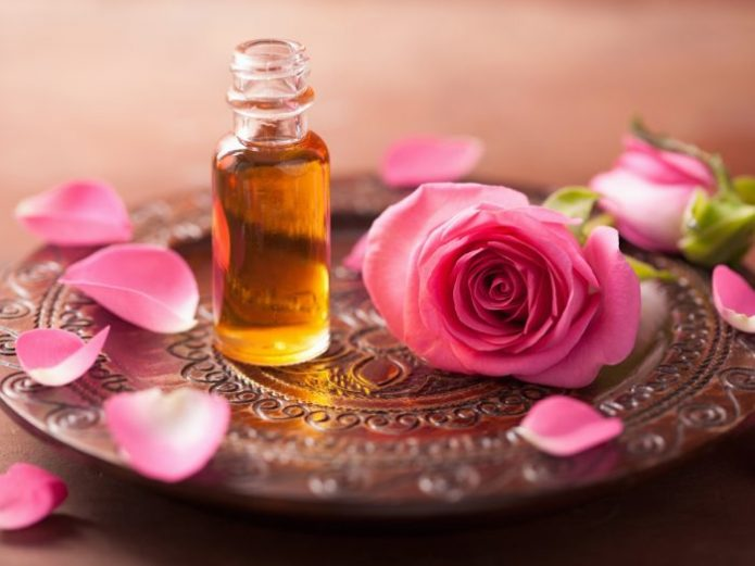 Бутылочка с маслом и цветок розы на резном блюде