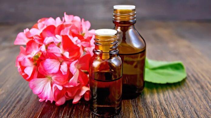 Две бутылочки масла и цветок герани
