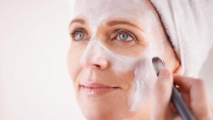 Женщине средних лет наносят маску кистью на лицо