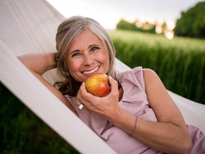 Женщина в возрасте 50–60 лет с яблоком в руке