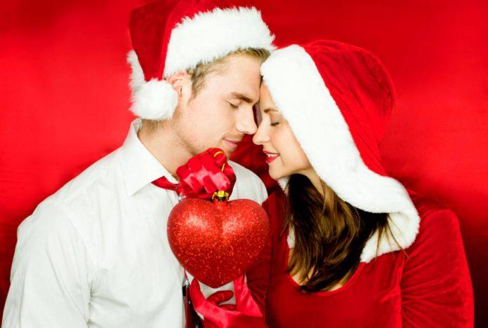 влюблённая пара в новогодних колпачках, сердце, красный фон
