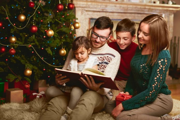 семья с детьми читает книгу возле новогодней ели