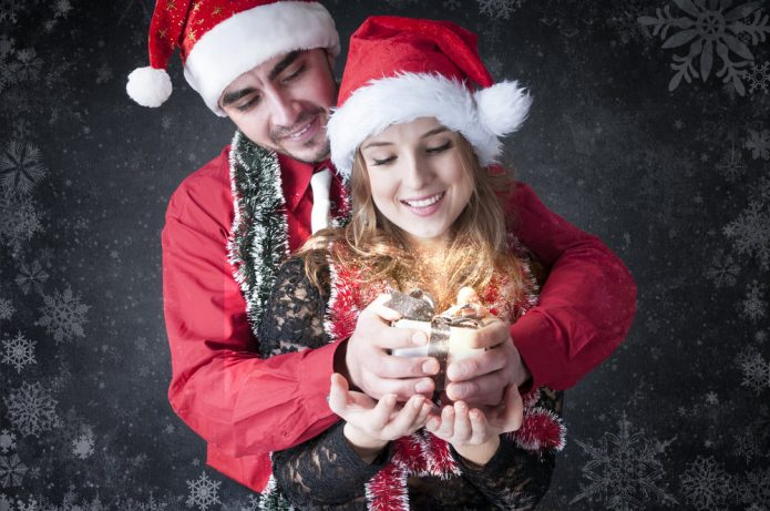 влюблённые в новогодних шапочках, подарок, темный фон со снежинками