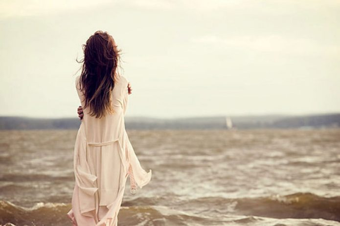 Девушка обнимает себя за плечи на берегу реки