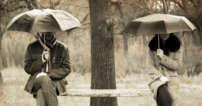 Пара под зонтами на разных концах лавки