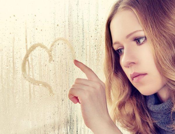 Грустная девушка рисует сердце на стекле