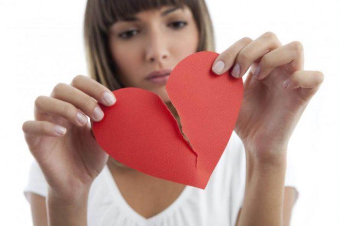 Девушка держит две половинки бумажного разорванного сердца