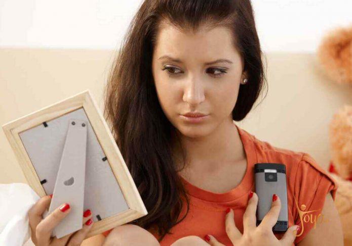 Девушка держит телефон и фото любимого