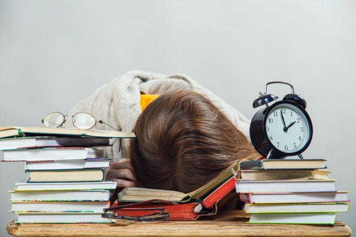 Девушка заснула за учебниками