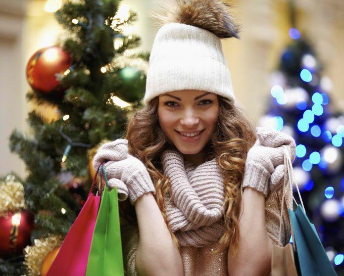 девушка с покупками на фоне новогодних ёлок