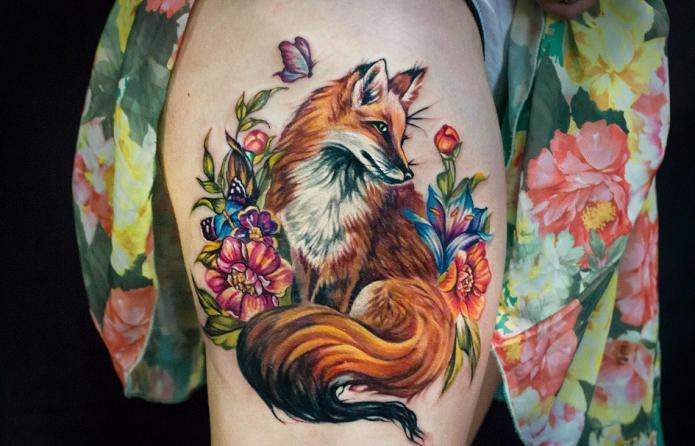 тату лисица в в цветах на женском бедре