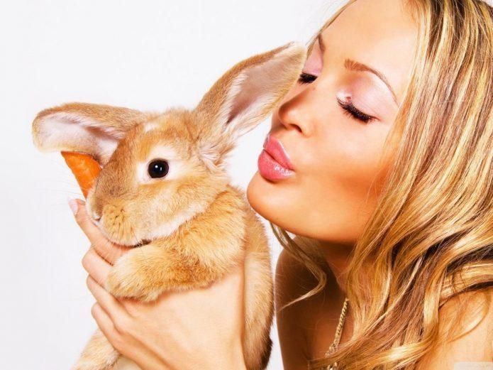 девушка целует рыжего кролика