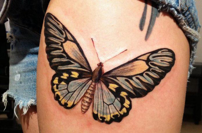 тату бабочка в цвете на женском бедре