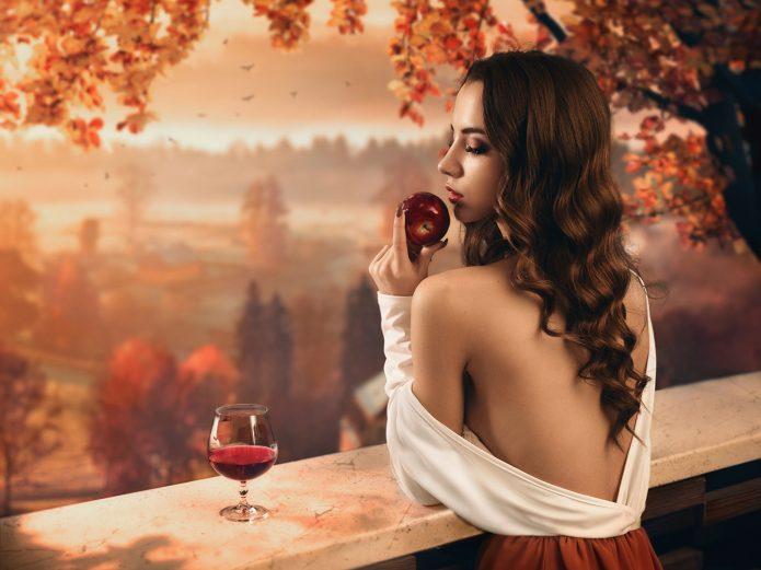Женщина с бокалом вина и яблоком в осеннем пейзаже