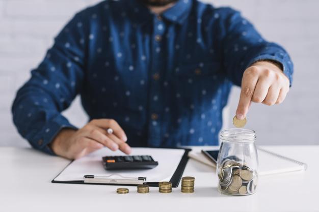 мужчина складывает монеты в банку