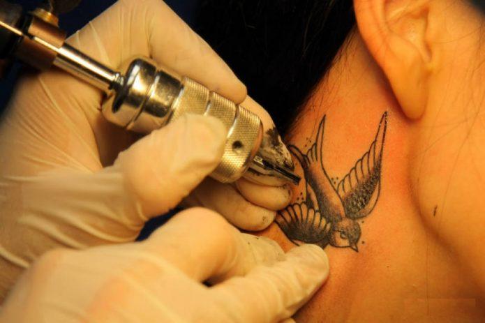 татуировщик набивает ласточку на шее