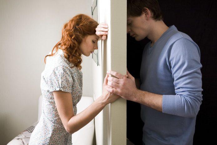 Печальные парень и девушка по разные стороны двери