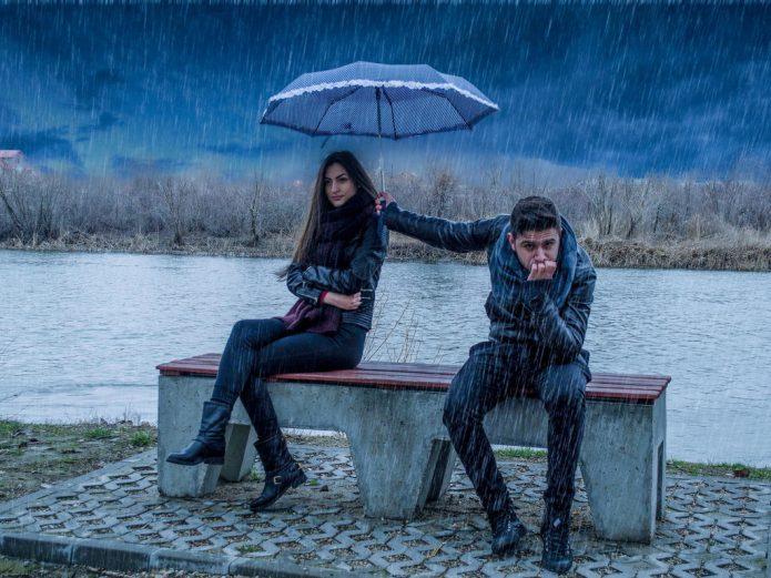Расстроенный мужчина держит над обиженной женщиной зонт