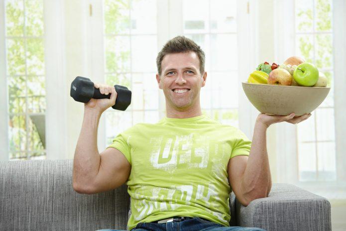 Здоровый мужчина с фруктами и гантелей