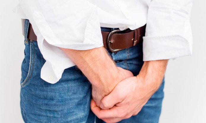 Мужчина держит руки на области паха