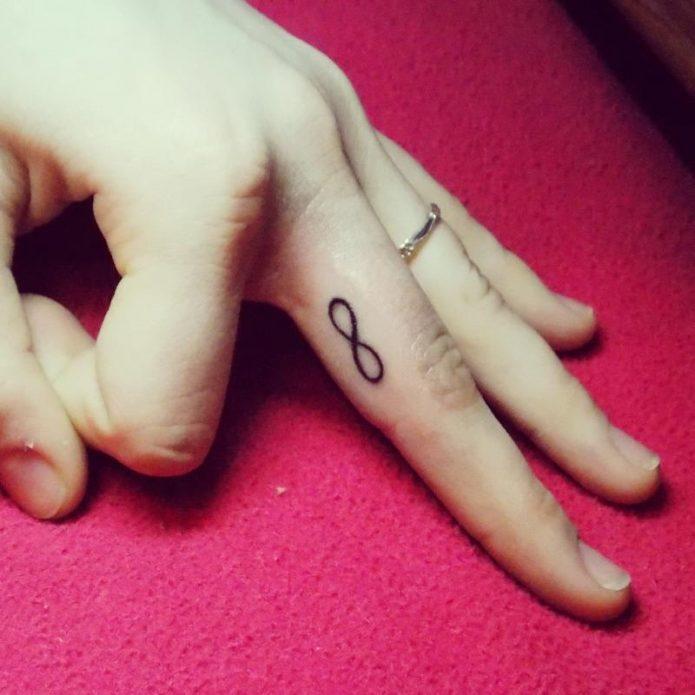 мини тату знак бесконечности на среднем пальце