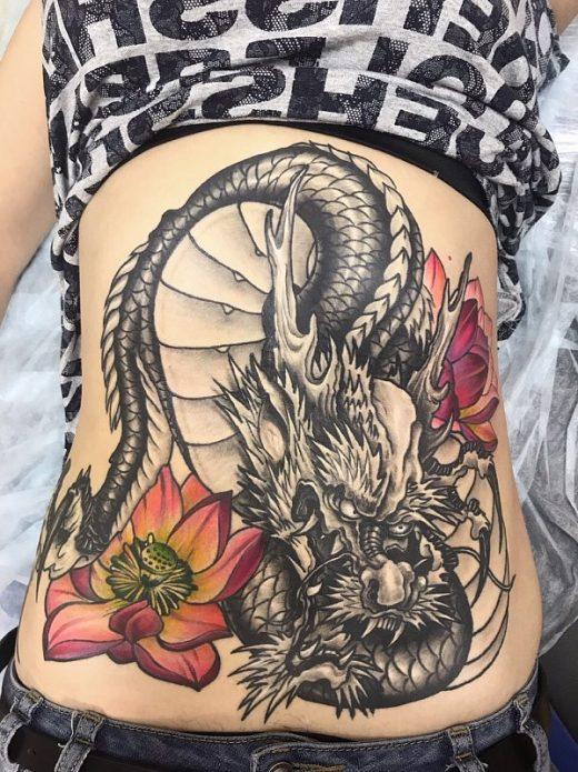 большая татуировка дракон с цветами на животе