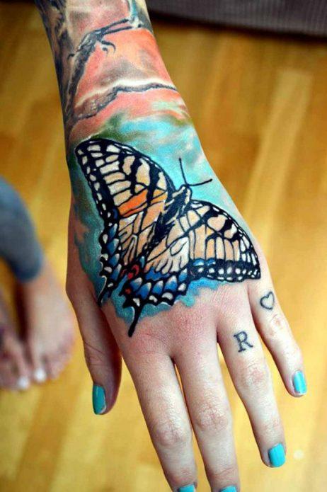 большая бабочка на голубом фоне татуировка на кисти руки
