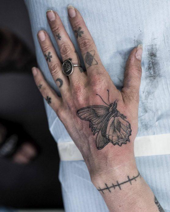 небольшой мотылёк на кисть руки монохромная тату